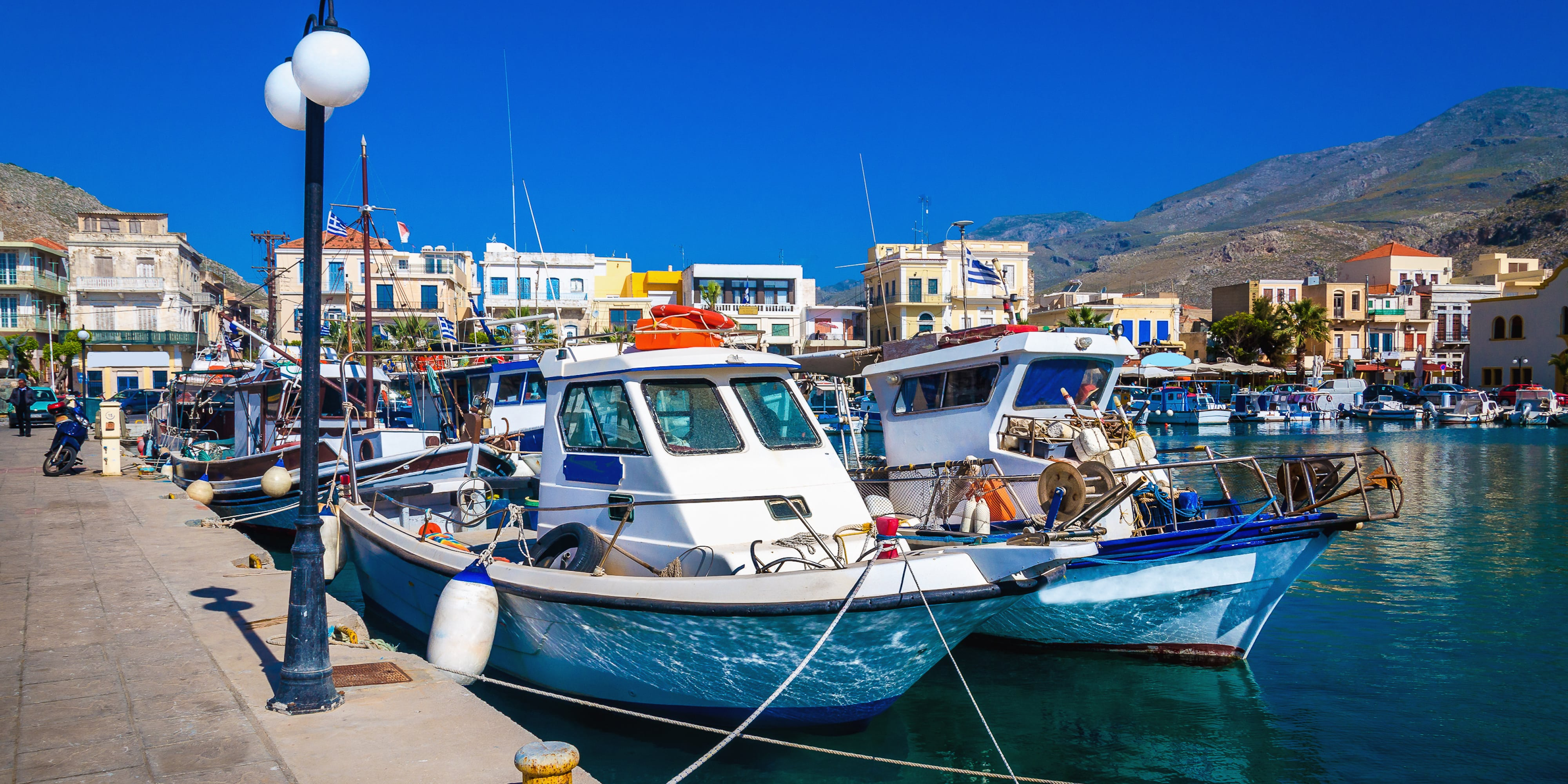 Wharf with citylights and cosy traditional Greek boats in small port of Pothia, Kalymnos, Greece